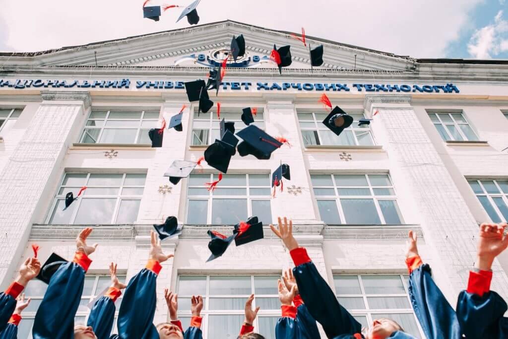 大学の卒業式で帽子を投げる人々